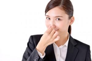 臭いと鼻をつまむ女性